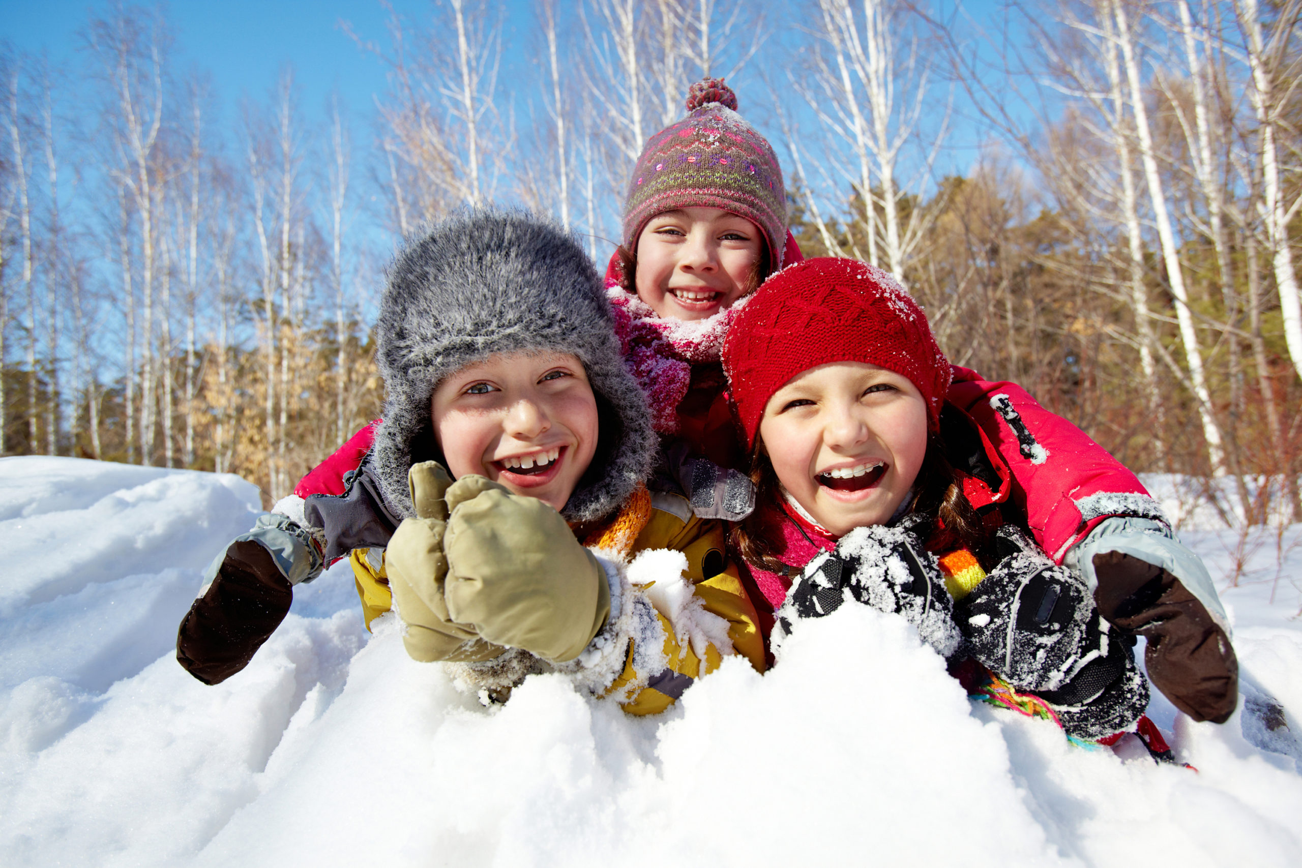 3 kids in snow pile laughing